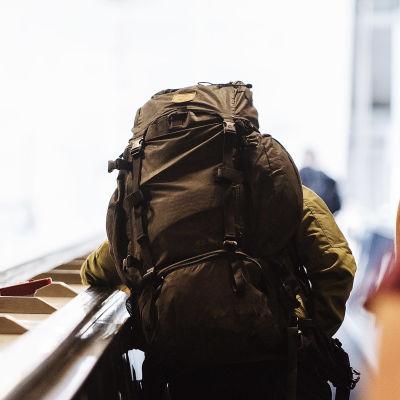 Resenärer med stora ryggsäckar står i en rulltrappa på Helsingfors-Vanda flygfält.
