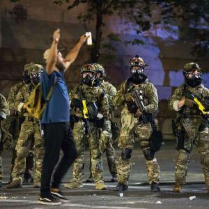 Mielenosoittaja kävelee sotilasasuisten erikoisjoukkojen edessä Portlandissa.