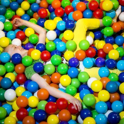 Lapsi on puoliksi piiloutunut kirkuvankirjavaan pallomereen.