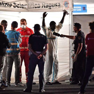 Poliisi skannaa siirtolaisen vaatteita.