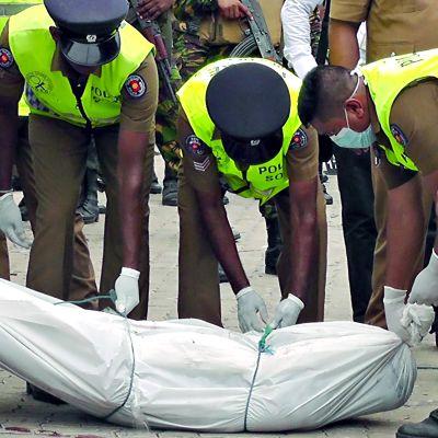 Poliisit siirtävät ruumista valkoisessa muovipussissa pois tapahtumapaikalta Sri Lanka Kalmunaissa.