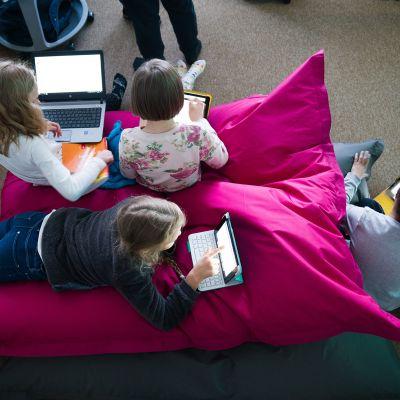 Peruskoululaiset opiskelevat. Alakouluikäisiä uudenlaisessa oppimisympäristössä padeineen ja kannettavine tietokoneineen.