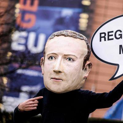 """Mielenosoittaja jolla on Mark Zuckerberg naamari kasvoillaan pitäen pahvista puhekuplaa """"regulate me!"""""""