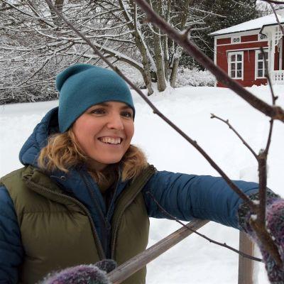 Lena Gillberg invid ungt äppelträd framför Strömsövillan