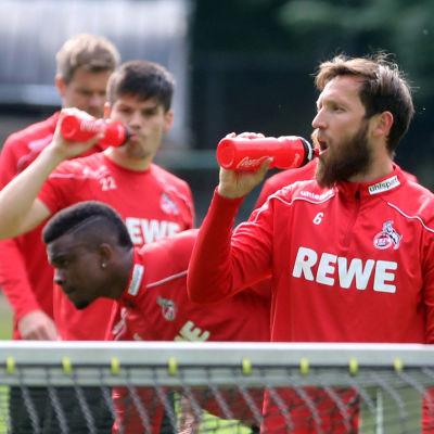 Marco Höger dricker vatten framför lagkamrater.