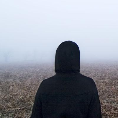 Människa med svart jacka står med ryggen vänd mot kameran och blickar ut över regnigt landskap