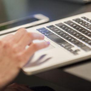 Käsi käyttää kannettavaa tietokonetta, vieressä pöydällä kännykkä