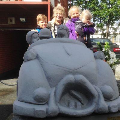 Päivi Kinnunen veistämässään Aku Ankka -betoniautossa lastenlastensa Konstan, Annikan ja Josefiinan kanssa.