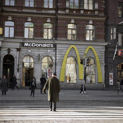 Mies ylittää suojatietä Mannerheimintiellä.