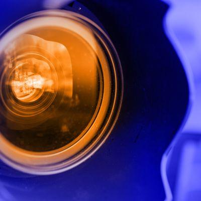 Oranssi kameralinssi sinisessa ympäristössä.