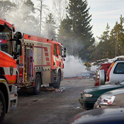 Palomies sammuttaa palavia roskia Pasilassa.