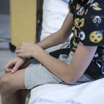 Poika istuu sairaalavuoteella.