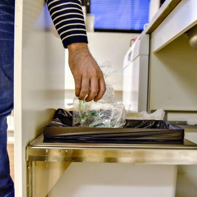 Mies laittaa muoviroskaa roskapussiin.