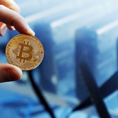 Bitcoin -kolikko miehen vasemmassa kädessä.