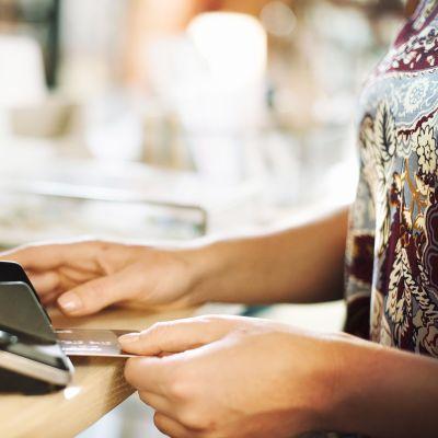 Nainen asettaa luottokorttia maksupäätteeseen.