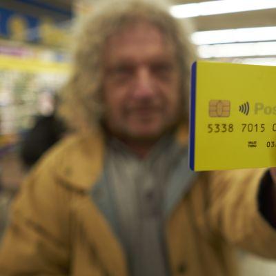 Mies pitää keltaista luottokortin näköistä muovikorttia kameran edessä. Kortissa on siru ja siinä lukee Posteitaliane.