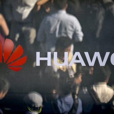 Huawein logo isossa mainosscreenissä johon heijastuu kadulla kävelevien ihmisten profiileja.