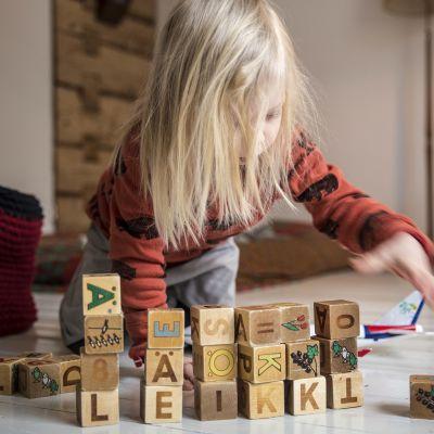lapsi leikkii kirjainpalikoilla