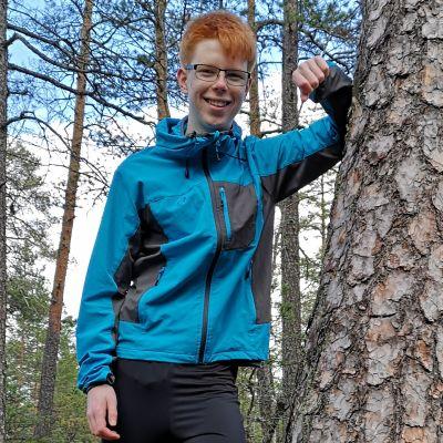 Kirkkonummelainen Eelis Ojala nojaa männyn runkoon. Ojalalle metsä ja ympäristö ovat tärkeitä ja hän myöntää, että ammatti saattaa löytyä näiden teemojen alta, mutta myös muutkin alat kiinnostavat.
