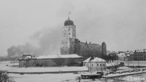 Viborg slott med finska flaggan höjd medan Viborg stad brinner i bakgrunden under slutskedet av vinterkriget. SA-kuva.