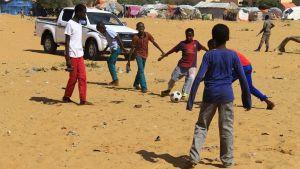 Interna flyktingbarn spelar fotboll, säkerhetsvakt uppe i högra hörnet.
