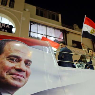 Egyptin presidentin tukijoita auton lavalla, auton kyljessä presidentti Sisin kasvot.