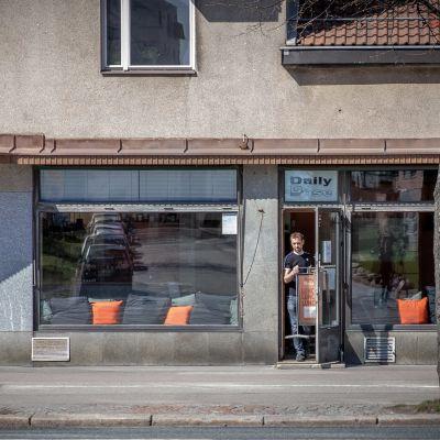 Mies nostaa lounaskylttiä  ravintolan edustalle.