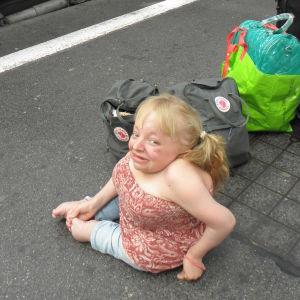 Monitaituri Noora Västinen istuu rautatieaseman laiturilla reppujen ja laukkujen vierellä interrail-reissullaan.