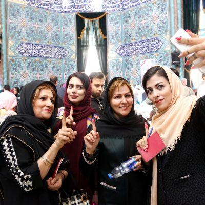 Neljä naista hymyilee selfiessä, taustalla koristeellinen sininen seinä.