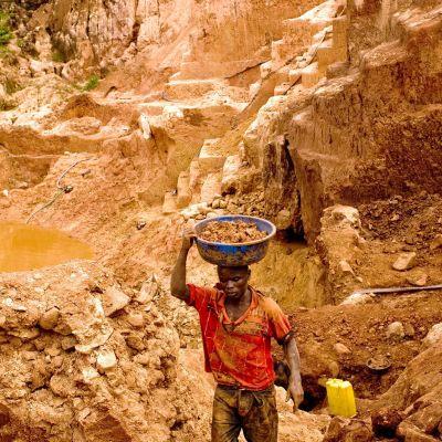 Kultakaivoksen työntekijä kantaa maa-ainesta huuhdottavaksi.