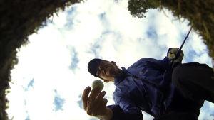 Mies poimii golfpallon reiästä.