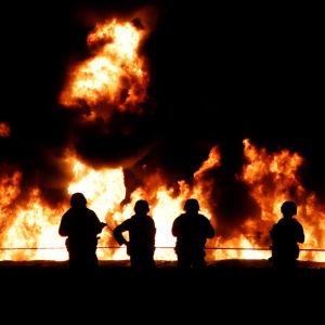 Stora lågor mot en mörk natthimmel sedan ett oljerör börjat brinna i i delstaten Hidalgo i Mexiko. I förgrunden fyra människor.