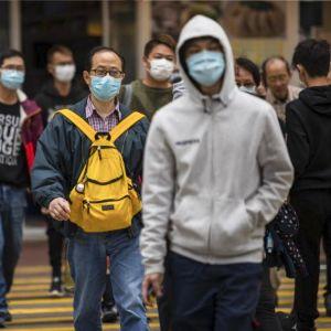 Aasialaisia ihmisiä kävelee kadulla kasvosuojaimet yllään.