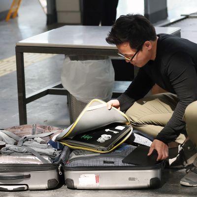 Lentomatkustaja avaa matkalaukkunsa lentokentän turvatarkastuksessa.