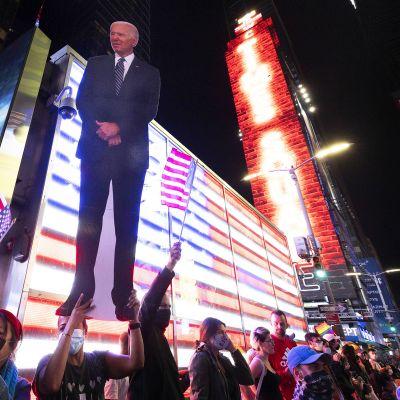 Vaalivoittoa juhlivia ihmisiä Times Squarella.