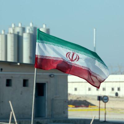 Iranin lippu ydinvoimalaitoksen edustalla.