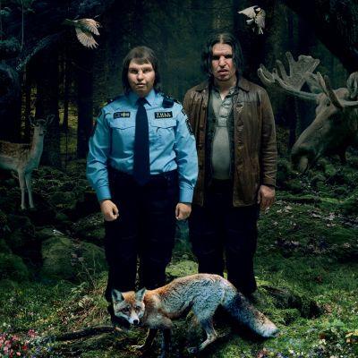 Tina (Eva Melander) och Vore (Eero Milonoff) står bredvid varandra i skogen. Planschbild för filmen Gräns.