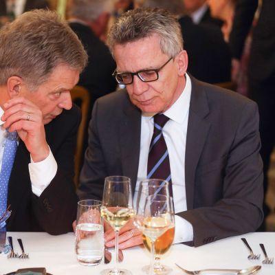 Sauli Niinistö  ja Thomas de Maiziere keskustelevat Münchenin turvallisuuskokouksen vastaanotolla 18 helmikuuta. 2017.