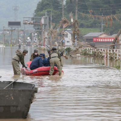 Japanin puolustusvoimat ja poliisi pelastamassa hoitokodin asukkaita tulvan keskellä.