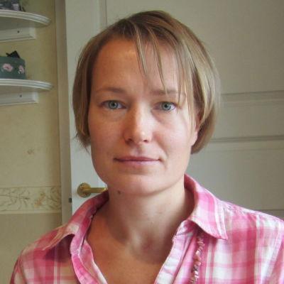 Linda Karlström sitter vid ett bord.