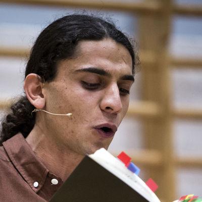 Hassan läser högt ur en bok.