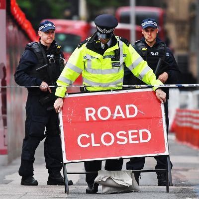 Poliisi asettelee tie suljettu -kylttiä.