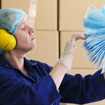 Tehtaan työntekijä tarkastelee hengityssuojainnippua Venäjällä.