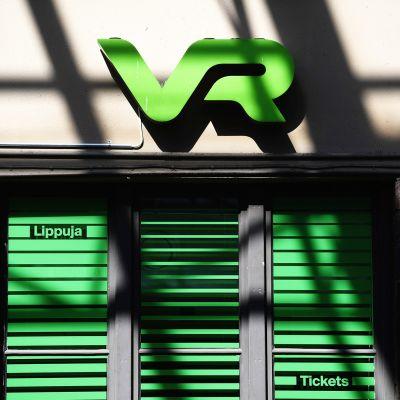 VR:n logo rautatieaseman seinässä.