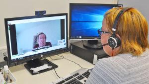 En kvinna sitter framför en dator. Hon har hörlurar på sig. På skärmen framför henne syns en äldre man som hon pratar med.