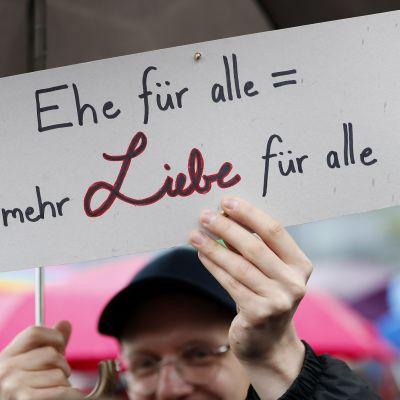 Mies pitelee kylttiä, jossa lukee saksaksi Avioliitto kaikille = Enemmän rakkautta kaikille.