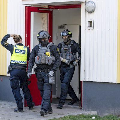 Mellakkapoliiseja talon edustalla Malmössä.
