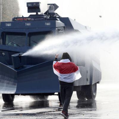 Valkovenäläinen mielenosoittaja uhmaa poliisin vesitykkiautoa.