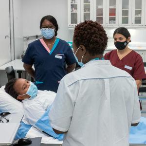 Hoitotyön lehtori Emma Tamankag ja sairaanhoitaja opiskelijat Alvina Njila, Mashal Ghaffar ja Esteban Marquesini ovat sairaalavuoteen äärellä ja vuoteessa potilasta esittää sairaanhoitaja opiskelija Lucy Mararia. Hoitotyön lehtori Tanja Hakkarainen oikea