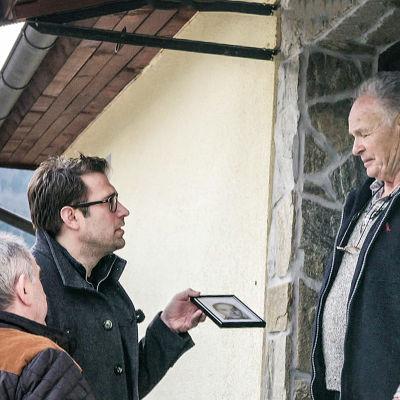 Programledare Niklas Källner visar upp ett foto för en man som står i en dörr.